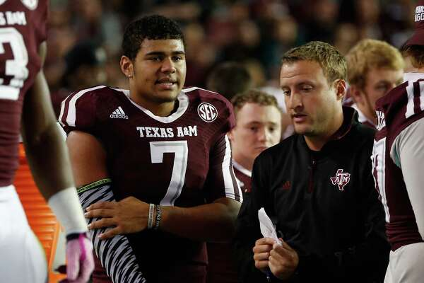 Kenny Hill of the Texas A&M Aggies chats with quarterbacks coach Jake Spavital during the first half against the Mississippi Rebels at Kyle Field on Oct. 11, 2014 in College Station.