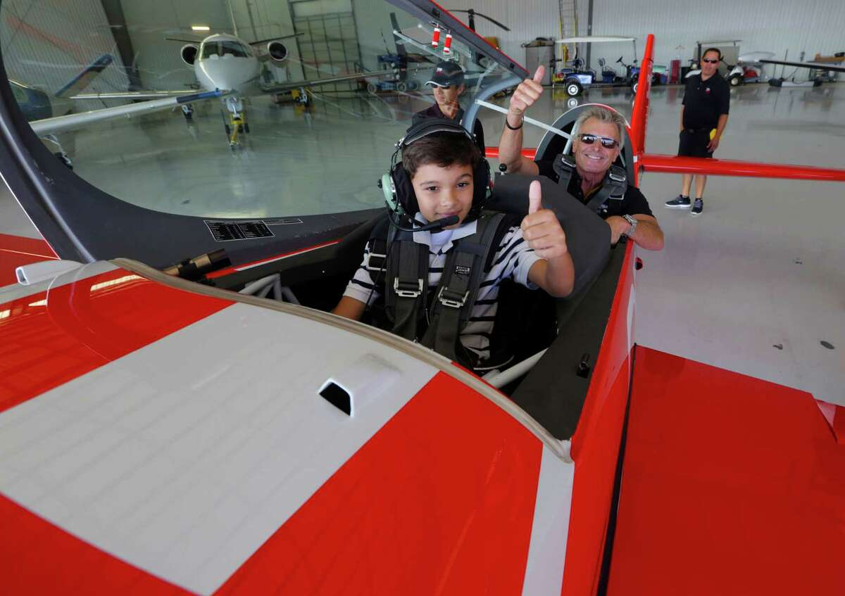 Ten year-old Ryan Glasgow gives the all go signal to renowned airshow pilot Sean D. Tucker before experiencing his first flight in the Team Oracle's Extra 300L as a Young Eagle with Thursday October 30, 2014 at Ellington Field in Houston, TX.