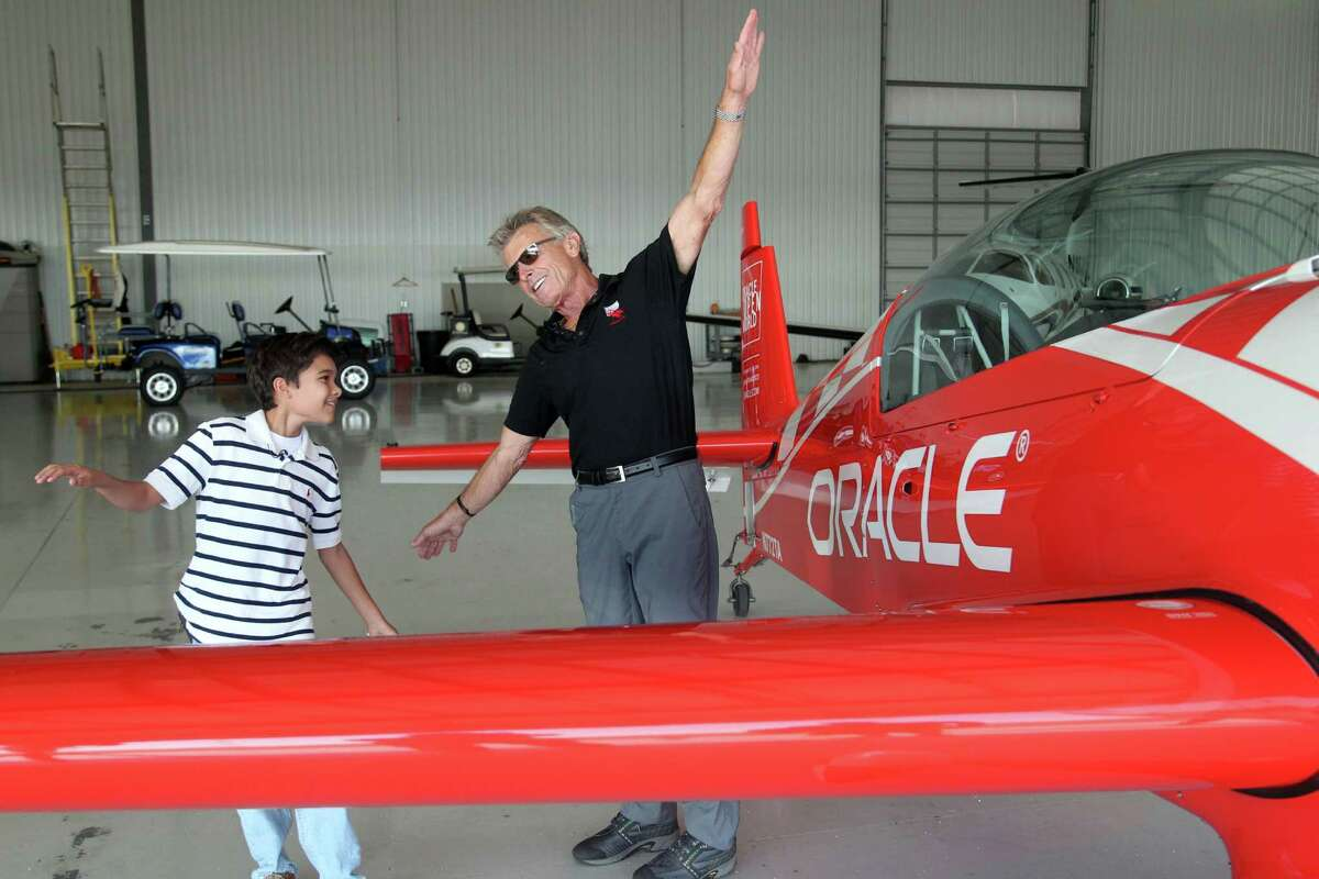 (l-r) Ten year-old Ryan Glasgow gets some flying tips from renowned airshow pilot Sean D. Tucker Thursday October 30, 2014 at Ellington Field in Houston, TX. Glasgow experienced his first flight in a general aviation aircraft as a Young Eagle with Young Eagles Chairman pilot Sean D. Tucker. Since 1992, more than 1.8 million Young Eagles have enjoyed a flight from the Experimental Aircraft Association's network of volunteer pilots. For many, it was the start of their journey to becoming a pilot, aircraft mechanic, air traffic controller.