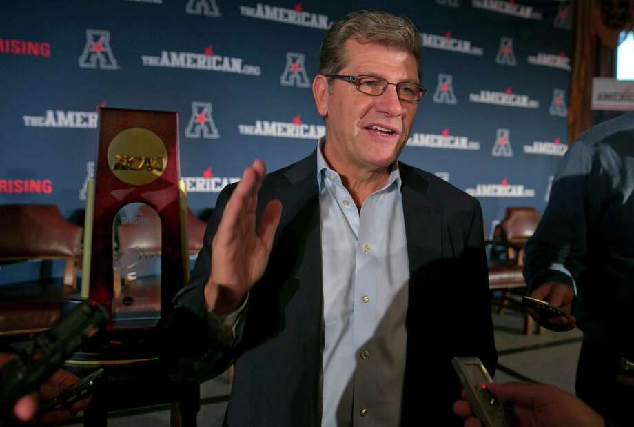 UConn head coach Geno Auriemma stands besides his team's NCAA championship trophy as he is interviewed during the American Athletic Conference women's NCAA college basketball media day, in New York,  Thursday, Oct. 30, 2014. (AP Photo/Richard Drew) Photo: Richard Drew, STF / AP