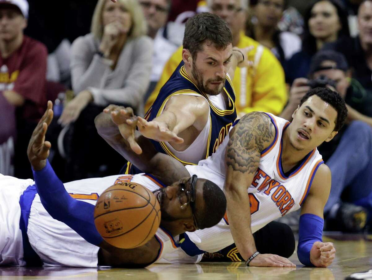 Cleveland Cavaliers' Kevin Love, top, battles for a loose ball with New York Knicks' Amar'e Stoudemire, left, and Shane Larkin in the first quarter of an NBA basketball game Thursday, Oct. 30, 2014, in Cleveland. (AP Photo/Tony Dejak) ORG XMIT: OHMD120