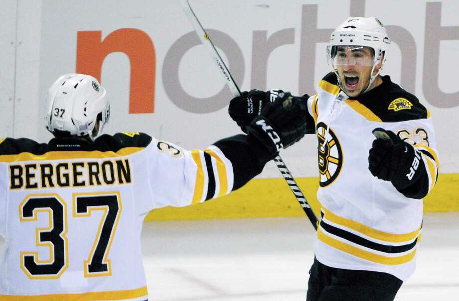 Boston Bruins' Patrice Bergeron (37) celebrates an overtime goal by teammate Brad Marchand (63) during an NHL hockey game against the Buffalo Sabres Thursday, Oct., 30, 2014, in  Buffalo , N.Y. Boston won 3-2. (AP Photo/Gary Wiepert) ORG XMIT: NYGW110 Photo: Gary Wiepert / FR170498 AP