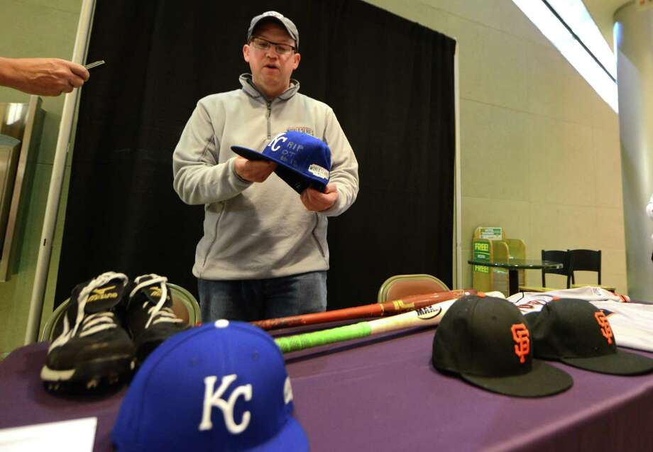 Brad Horn, vice president of communications for the National Baseball hall of Fame, displays Yordano Ventura's Kansas City Royals baseball hat with a group of Cooperstown bound artifacts from Wednesday's World Series game 7 against the San Francisco Giants and the Kansas City Royals at Albany International Airport Thursday, Oct. 30, 2014, in Colonie, N.Y. The hats pays tribute to Cardinals outfielder Oscar Taveras. The other items included hats from Giants' Madison Bumgarner and manger Bruce Bochy; Royals hat from Brandon Finnegan; a Jersey from Buster Posey of the of the Giants; a pair of cleats from San Francisco Giants pitcher Jeremy Affeldt worn in game 7 and bats from Giants' Hunter Pence and Royals Salvador Perez. (Will Waldron/Times Union) Photo: WW / 00029255A