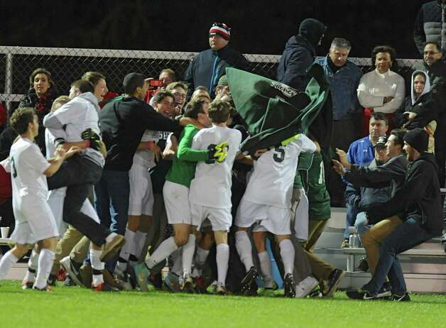 Shenendehowa's Tom Osborn is buried in a mass of celebration after making the winning score during the Class AA boys' semifinal soccer game against Guilderland on Thursday, Oct. 30, 2014 in Colonie, N.Y.  (Lori Van Buren / Times Union) Photo: Lori Van Buren / 00029248A