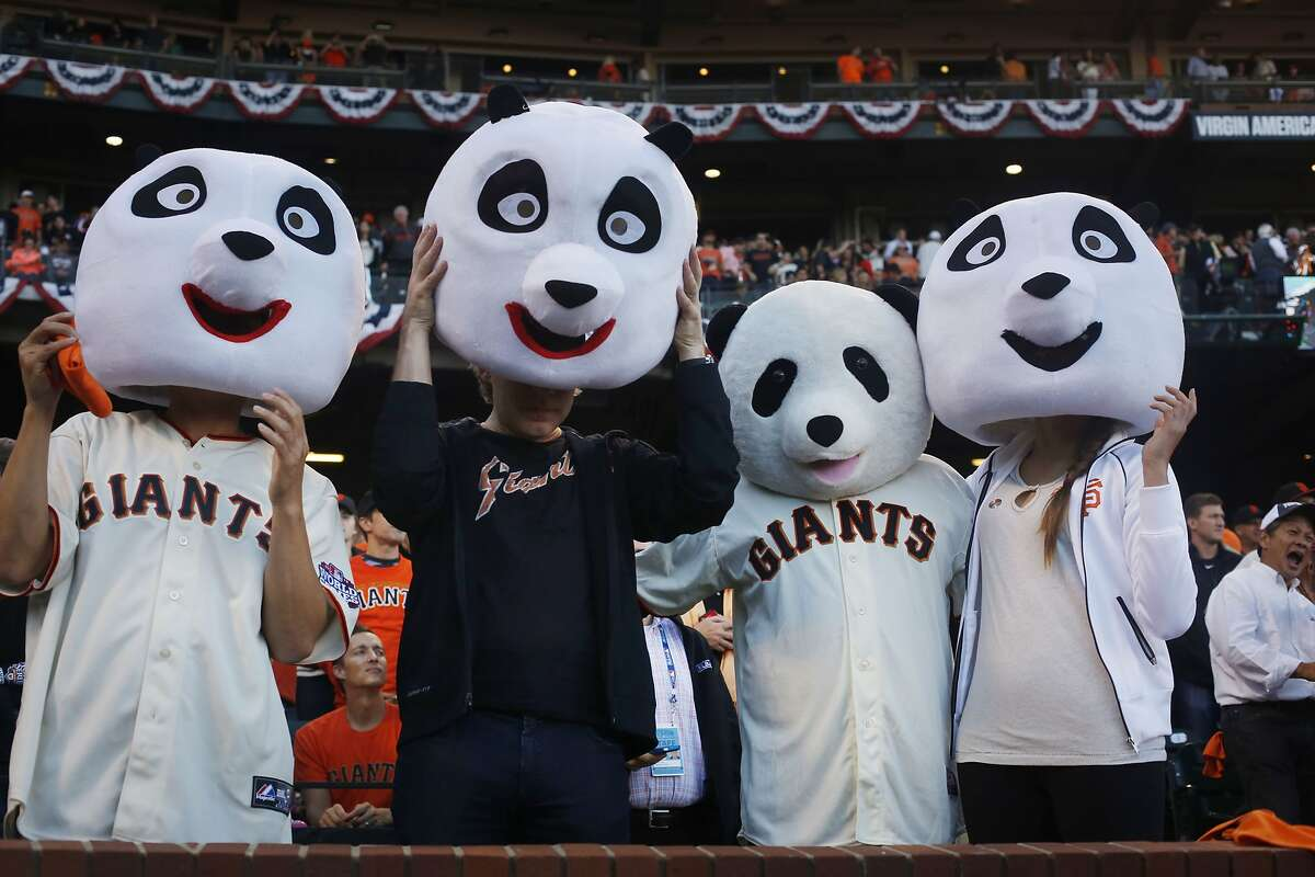Giants fans known for wearing larger-than-life panda heads Jimmy Wong, Michael Jessen, Sam Wong and Bianca Ruiz put their heads on after the singing of the national anthem at the start of game five of the World Series against the Kansas City Royals at AT&T Park on Sunday Oct. 26, 2014 in San Francisco, Calf.