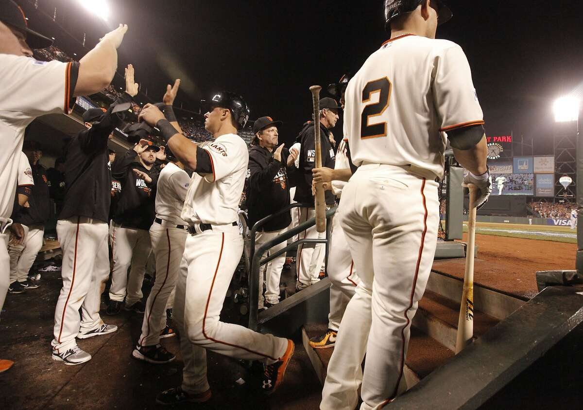 Giants' Joe Panik, (left center) scores on a Hunter Pence single in the fifth inning, as the San Francisco Giants went on to beat the Kansas City Royals 11-4 in game four of the World Series at AT&T Park in San Francisco, on Saturday Oct.25, 2014.