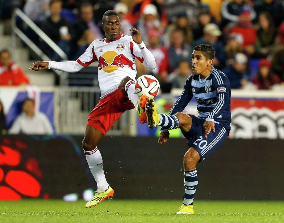 New York Red Bulls midfielder Lloyd Sam, left, battles Sporting Kansas City midfielder Jorge Claros (20) for the ball in the first half during an MLS playoff soccer match at Red Bull Arena in Harrison, N.J., Thursday, Oct. 30, 2014. (AP Photo/Rich Schultz) Photo: Rich Schultz / Associated Press / FR27227 AP