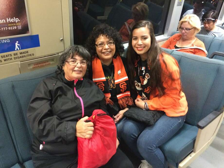 Martha Rodriguez (left), her sister Yvette Carmona, and Carmona's 17-year-old daughter, Serena Carmona-Hester, caught a pre-dawn BART train from Pleasanton Friday, Oct. 31, 2014, to get a good seat for the Giants World Series Parade in San Francisco. Serena played softball with the sister of Giants shortstop Brandon Crawford and was coached by his dad. Photo: Demian Bulwa, The Chronicle