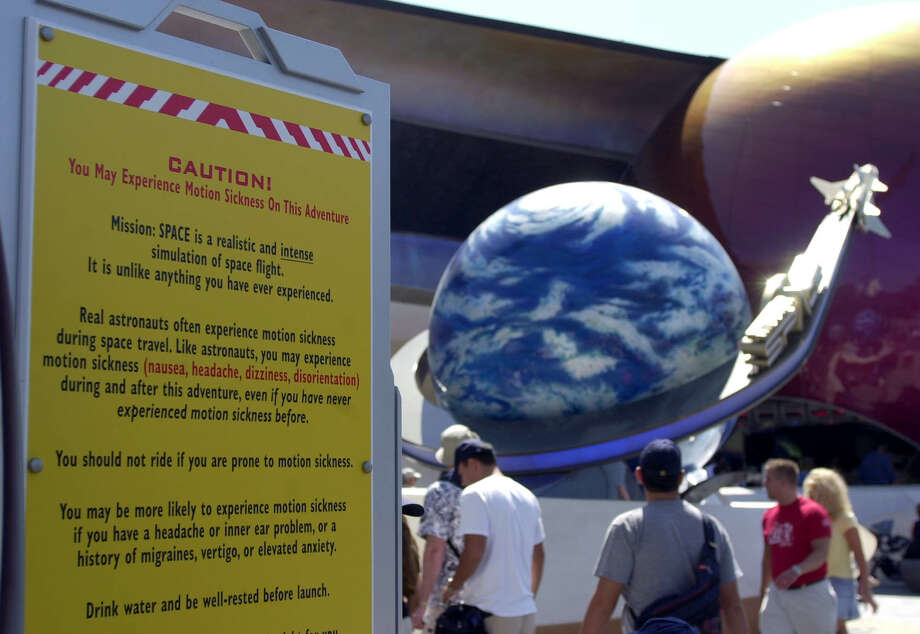 A caution sign alerts guests at Walt Disney World's Mission:Space that they may experience motion sickness on this ride. Photo: PETER COSGROVE, STF / AP