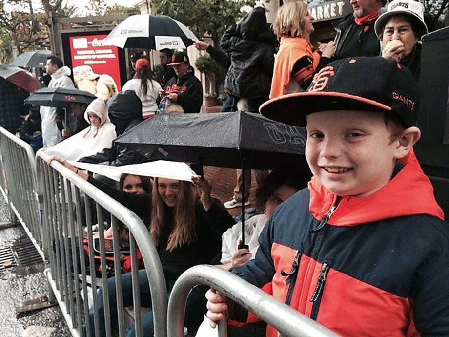 Jakob Hilton,7 (right) waits for the SF Giants World Series parade on Fri. Oct. 31, 2014. He's not playing hooky. Sonoma schools were out today. Photo: Jill Tucker, The Chronicle