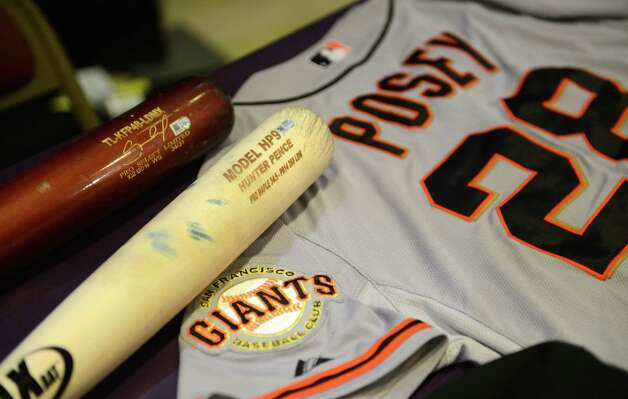 Bats from Salvador Perez of the Kansas City Royals and Hunter Pence San Francisco Giants are displayed with a Champaign drenched World Series jersey from Buster Posey of the of the Giants during a display of World Series artifacts which were being delivered to the Baseball Hall of Fame and Museum in Cooperstown Thursday, Oct. 30, 2014, at Albany International Airport in Colonie, N.Y. Other Hall of Fame artifacts included hats from Giants' Madison Bumgarner and manger Bruce Bochy; Royals hats from Brandon Finnegan and Yordano Ventura and a pair of cleats from San Francisco Giants pitcher Jeremy Affeldt worn in game 7. (Will Waldron/Times Union) Photo: WW / 00029255A