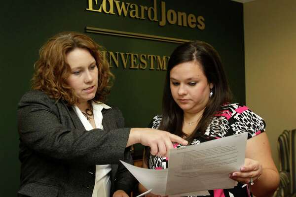 Candace Shotts, left, a branch office administrator, and Kelly Troutman, right, an on-call branch office administrator, are shown working at Edward Jones Investments, 1710 W. Lake Houston Parkway, Wednesday, Oct. 1, 2014, in Kingwood.