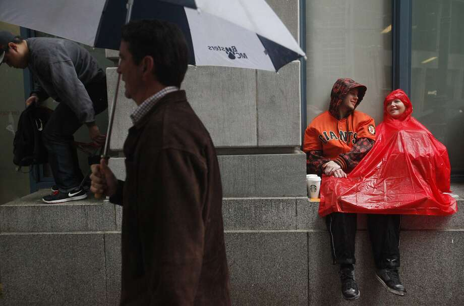 Michael Barton, left, sits against a building out of the rain with his mother Janice Barton of San Jose before the World Series Parade celebrating the victorious San Francisco Giants Oct. 31, 2014 in downtown San Francisco, Calif. The Giants won the World Series 4-3 against the Kansas City Royals on Wednesday night. The celebration parade was held on Friday starting at Market and Steuart Streets and ended at Civic Center Plaza. Photo: Leah Millis, The Chronicle