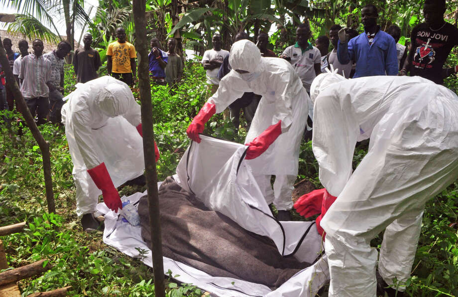 Hearth workers cover the body of a man suspected of dying from the Ebola virus on the outskirts of Monrovia, Liberia. Some 5,000 people have died from the virus. Photo: Abbas Dulleh / Associated Press / AP