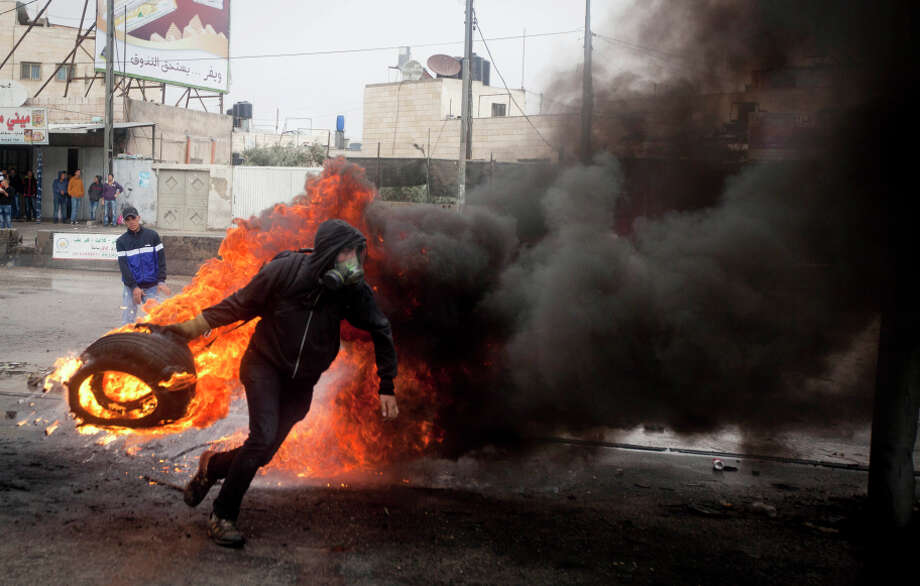 A Palestinian throws a burning tire during clashes with Israeli troops at a checkpoint near the West Bank city of Ramallah. Photo: Majdi Mohammed / Associated Press / AP