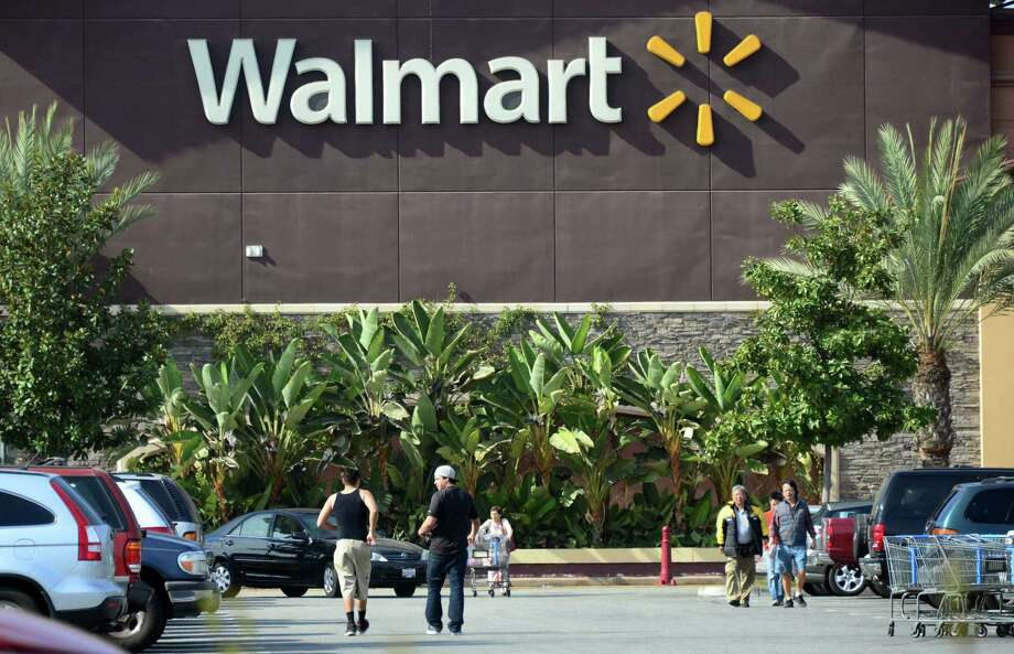 (FILES) This January 29, 2014 file photo shows shoppers outside a Walmart store in Rosemead, California. US retail king Wal-Mart announced October 7, 2104 that it is eliminating health benefits to some 30,000 employees to control rising healthcare costs. The cuts would apply to those employees working fewer than 30 hours per week. AFP PHOTO / FREDERIC J. BROWN / FILESFREDERIC J. BROWN/AFP/Getty Images Photo: FREDERIC J. BROWN / Frederic J. Brown / AFP / Getty Images / AFP