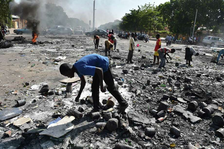 People pick up items on the avenue leading to the burnt parliament in Ouagadougou a day after it was stormed by protesters demanding President Blaise Compaore quit immediately. Photo: ISSOUF SANOGO / AFP/Getty Images / AFP