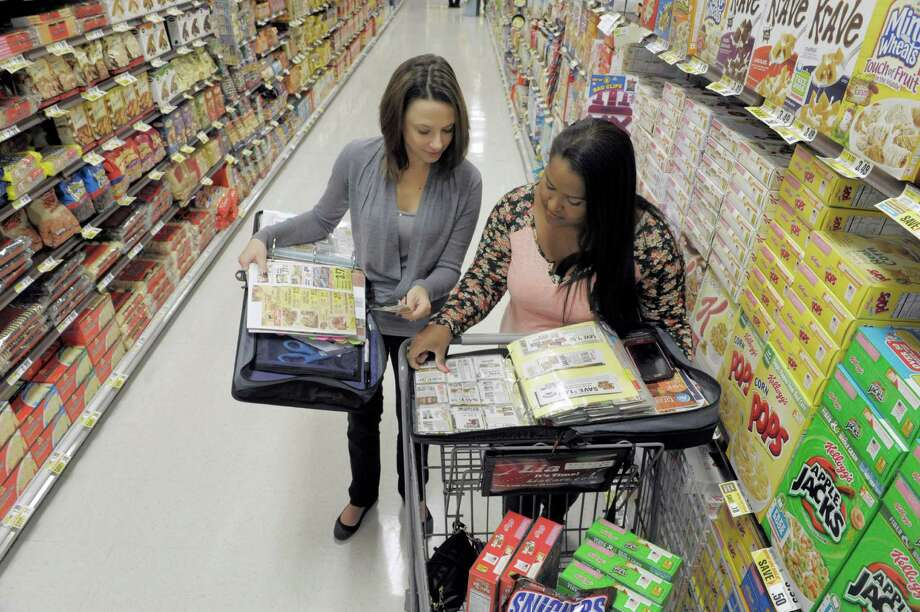 Melissa Verga, left, and Priscila Melendez, founders of a local charitable venture called Couponers for a Cause, look through their coupon binders at ShopRite on Tuesday, Oct. 28, 2014, in Niskyuna, N.Y.  (Paul Buckowski / Times Union) Photo: Paul Buckowski / 00029144A