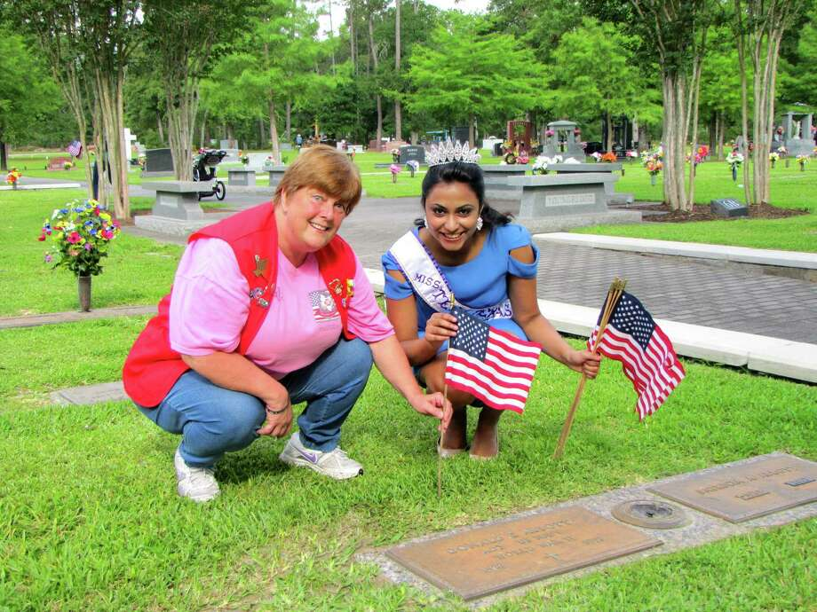 Paula Ison, left, president of The Woodlands Veterans of Foreign Wars, and Miss Teen Texas International 2014 Jahnavi Muppaneni place flags on veterans' graves. Photo: Picasa