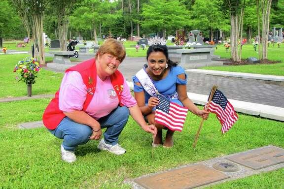 Paula Ison, left, president of The Woodlands Veterans of Foreign Wars, and Miss Teen Texas International 2014 Jahnavi Muppaneni place flags on veterans' graves.