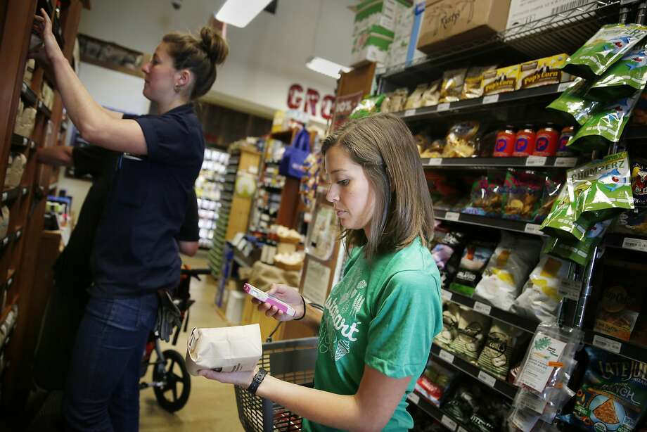 Instacart personal shopper, Sydney Hollingsworth, scans the UPC code on a product as she fills a customer's order at the Bi-Rite Market on Divisadero Street on Thursday, July 24,  2014 in San Francisco, Calif. Photo: Lea Suzuki, The Chronicle