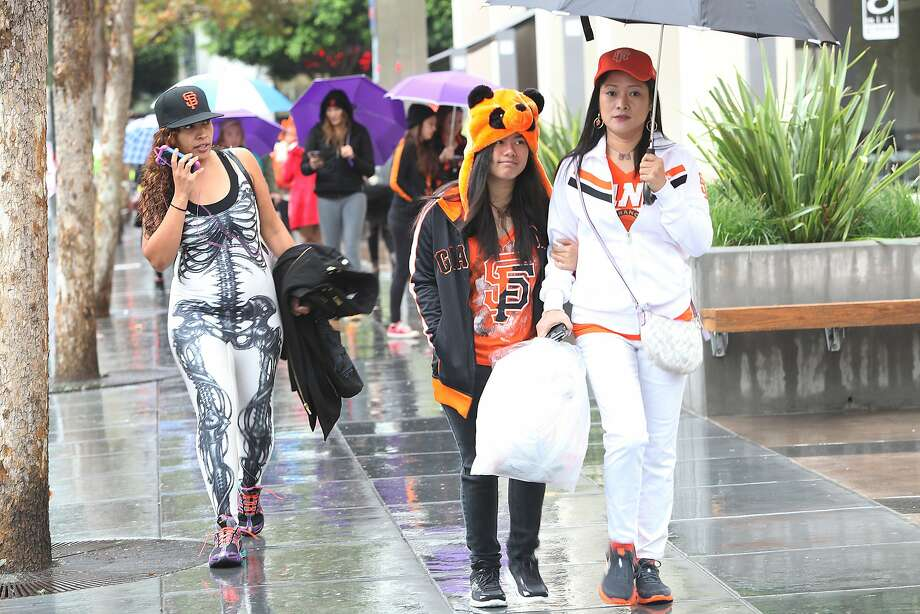 Monica D'Agostino (left) from San Francisco, and Maimee Amistad (middle) and her mother Fe Marie Amistad from Hercules walk in the rain on Mission St. toward the Giant's parade in San Francisco, Calif., on Friday, October 31, 2014. Photo: Liz Hafalia, The Chronicle