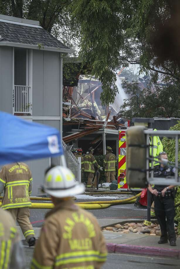 Firefighters stand in the street after an apartment explosion, thought to have been caused by a hash oil lab, in Walnut Creek last year. Two were injured in the explosion. Photo: Sam Wolson, Special To The Chronicle