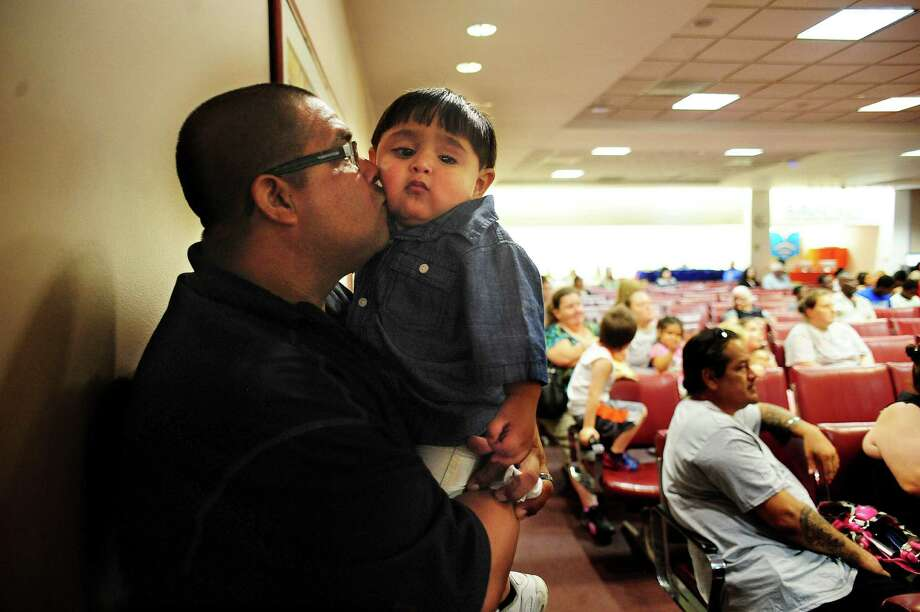 "John Gonzales holds ""Baby Jack,"" one of six children he and his wife, Laura, were adopting during a mass monthly adoption ceremony in the Bexar County Courthouse in August. November is National Adoption Month. Photo: Billy Calzada / Billy Calzada / San Antonio Express-News / San Antonio Express-News"