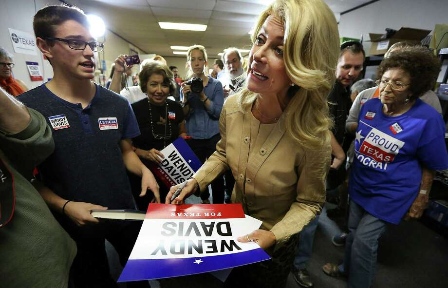 Senator Wendy Davis signs posters as she makes a stop in San Antonio at her Northeast Side field office, which is probably her last stop in San Antonio before election. At left is Gabrien Gregory who voted for the first time this year and Wandy Lay, right. Friday, Oct. 31, 2014. Photo: Bob Owen, San Antonio Express-News / ©2014 San Antonio Express-News