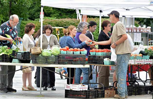 Ron Bulich, right, of Bulich Creek Farm in Leeds, with a line of customers at the Farmer's Market on the Empire State Plaza Friday August 15, 2014, in Albany, NY.  (John Carl D'Annibale / Times Union) Photo: John Carl D'Annibale