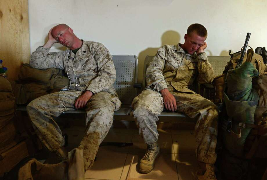 U.S .Marines rest on benches as they prepare to withdraw from the Camp Bastion-Leatherneck complex at Lashkar Gah in Helmand province, Afghanistan. With strikes by the terrorist group ISIS continuing, including the beheadings of journalists, a reader says a war-weary U.S. should think twice about escalating the war on terror. Photo: WAKIL KOHSAR / WAKIL KOHSAR / AFP/Getty Images / AFP