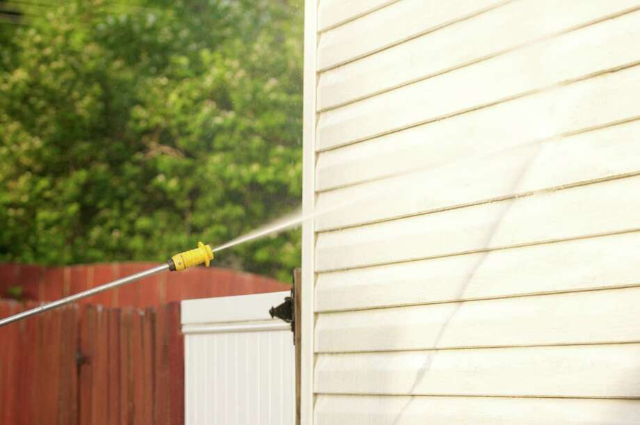 Use caution when power washing the exterior of the house. Start on the lowest pressure setting and never use chlorine bleach. pressure washing a dirty house Photo: Getty Images / (c) Arthur Carlo Franco