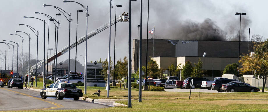 Firefighters battle a fire at Wichita Mid-Continent Airport  in Wichita, Kan., Thursday, after a  small-plane crash that killed a pilot and three people in a building. Photo: Mike Hutmacher / The Wichita Eagle / The Wichita Eagle