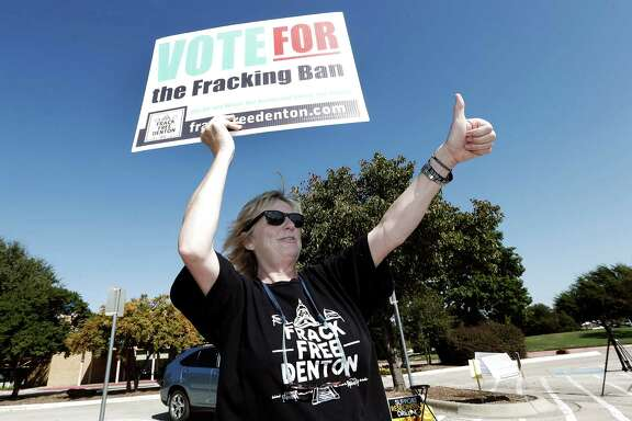 Anti-fracking advocate Cathy McMullen gives a thumbs up to passing motorist at the Denton Civic Center.