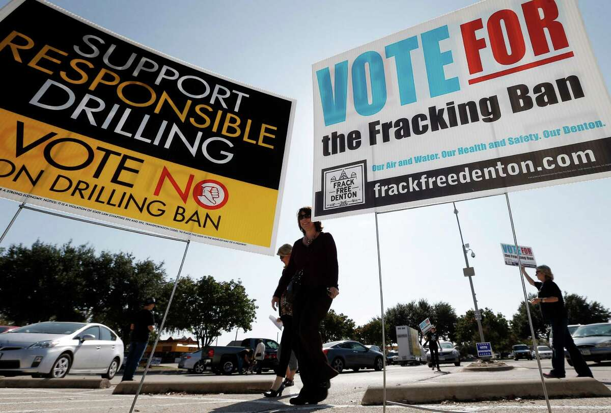 Cathy McMullen, holding a sign at right during a demonstration Oct. 30, led a successful drive to ban fracking in the city of Denton.