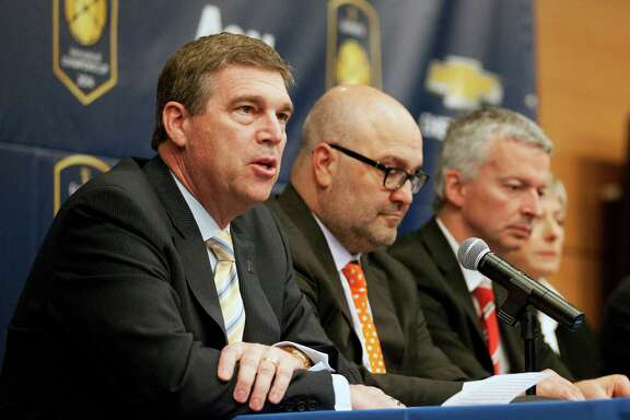 FILE - In this April 4, 2014, file photo, University of Michigan Director of Athletics Dave Brandon, left, speaks to the media during a news conference in Ann Arbor, Mich. Others are unidentified. Brandon has resigned, setting the stage for new leadership at the top of one of the nation's most prominent athletic departments.  (AP Photo/The Ann Arbor News, Patrick Record, File)  LOCAL TELEVISION OUT; LOCAL INTERNET OUT