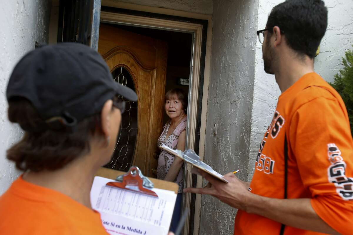 Margaret and Tomas Rebecchi (in Giants orange) talk with a Hollister, Calif. resident about supporting their anti-measure on the ballot Thursday October 30, 2014. In the upcoming election, three California counties will vote on ballot measures to ban fracking (hydraulic fracturing) within their borders. San Benito County's measure would also ban cyclic steam injection and acidization methods.