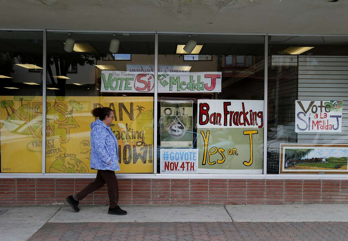 A woman walks by the Measure J campaign headquarters in downtown Hollister, Calif. Thursday October 30, 2014. In the upcoming election, three California counties will vote on ballot measures to ban fracking (hydraulic fracturing) within their borders. San Benito County's measure would also ban cyclic steam injection and acidization methods.