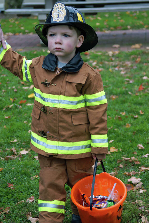 This young fireman was a one-man bucket brigade collecting candy during Trick or Treat on Safety Street. Photo: Genevieve Reilly / Fairfield Citizen