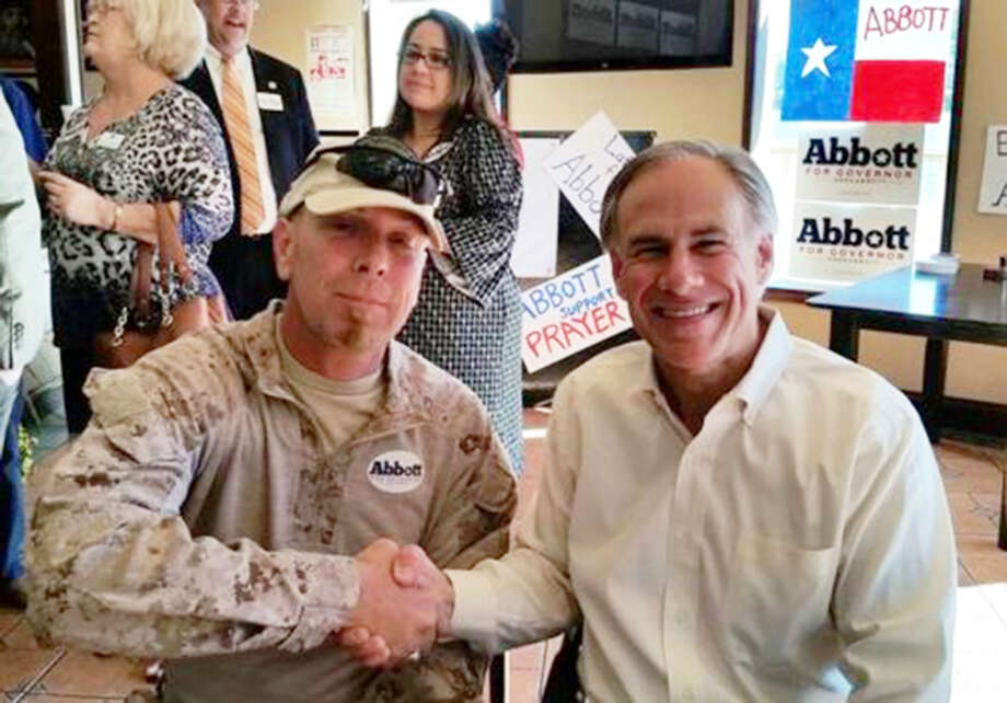 Greg Abbott poses with border militia member Kevin Lyndel Massey in Brownsville. Four days later, Masse was arrested on federal weapons charges.