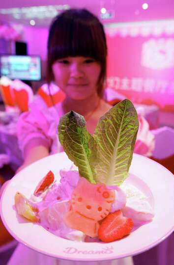 FILE - In this April 10, 2012 file photo, a waitress shows a dish at Asia's first Hello Kitty-theme