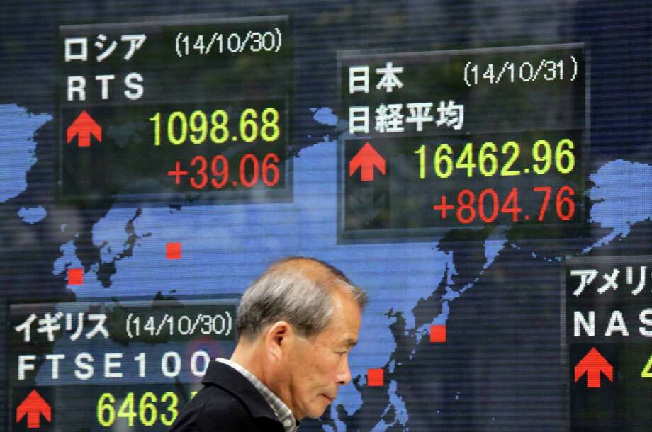A man walks past a security firm's electronic stock board in Tokyo. Japan's Nikkei 225 stock average surged 5 percent, and the yen slid against the dollar after the Bank of Japan unexpect edly an nounced new stimulus to boost a flagging economic recovery. Photo: Eugene Hoshiko / Associated Press / AP
