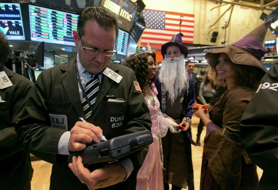 October had its scary moments on Wall Street, but on Halloween all was well as costumed characters distribute candy while Edward Curran works at the NYSE. Photo: Richard Drew, STF / AP