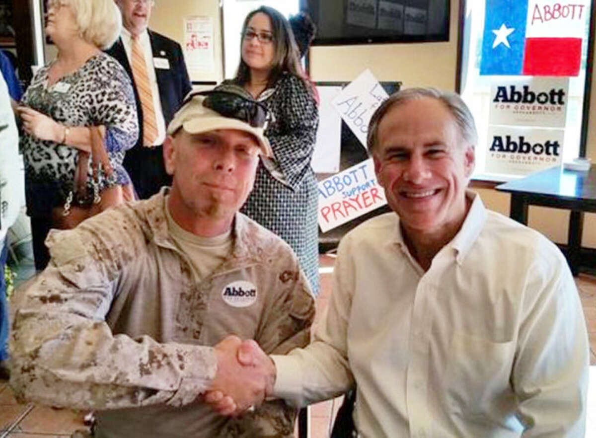 Republican gubernatorial candidate Greg Abbott (right) is seen posing with border militia member Kevin Massey at an Oct. 16 campaign event in Brownsville. Four days later, federal authorities arrested Massey on federal weapons charges.