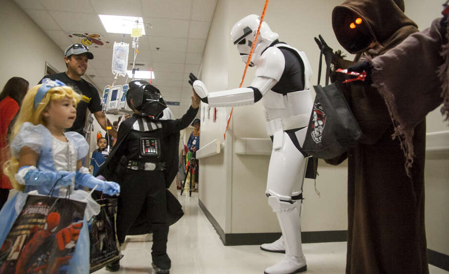 Roberto Banda III, 6, greets a stormtrooper Friday while trick-or-treating at the Children's Hospital of San Antonio. Photo: Julysa Sosa / For The San Antonio Express-News