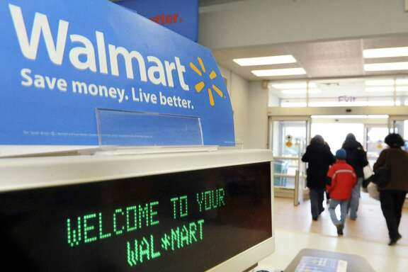 """In this Tuesday, Feb. 17, 2009, file photo, shoppers leave a Wal-Mart in Danvers, Mass.  Wal-Mart is doing whatever it takes to rope in holiday shoppers however they want to buy. For the first time, Wal-Mart Stores Inc. is offering free shipping on what it considers the season's top 100 hottest gifts, from board games to items related to Disney's hit film """"Frozen"""" items, starting Saturday, Nov. 1, 2014. The move comes as rival Target Corp. began offering free shipping on all items, a program that started late October and will last through Dec. 20. (AP Photo/Lisa Poole)"""