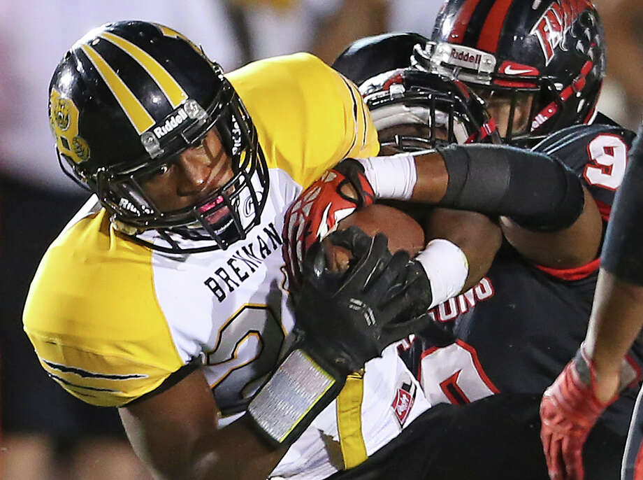 Falcon defenders try to strip Devonte Warren of the ball as he powers up the middle as Brennan plays Stevens at Gustafson Stadium on October 31, 2014. Photo: Tom Reel /San Antonio Express-News / San Antonio Express-News