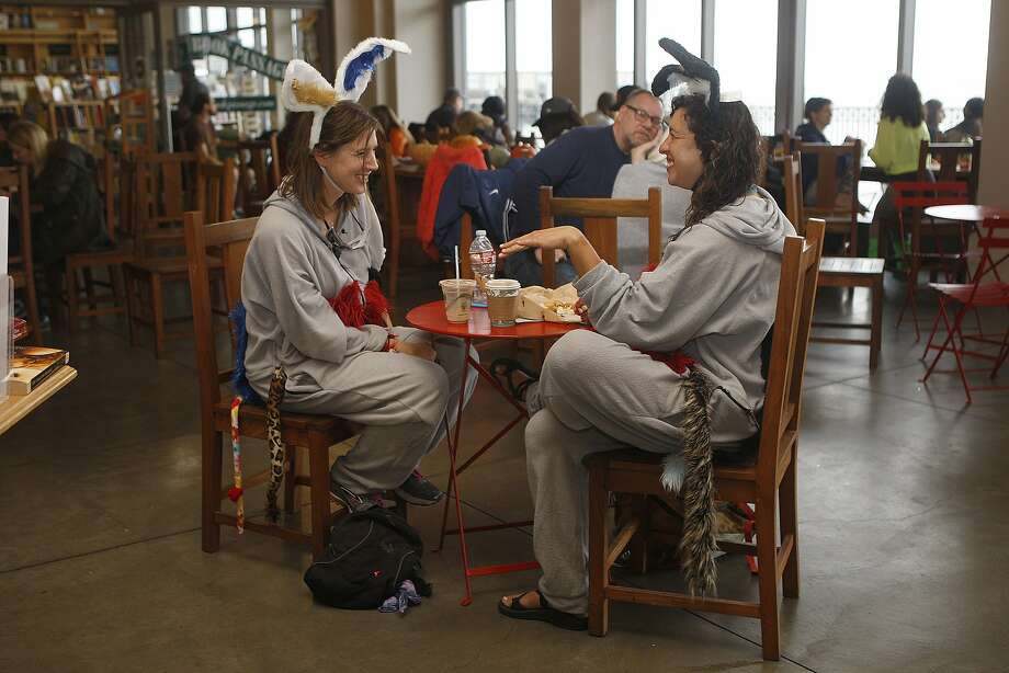 Lee Trope (left) has a chocolate milk as Callie Waldman (right) has a hot chocolate from Cowgirl Creamery in the Ferry building in San Francisco, Calif.,  as they wait for the start of the SF Giant's parade on Friday, October 31, 2014.  They are dressed as donkeys for Halloween. Photo: Liz Hafalia, The Chronicle
