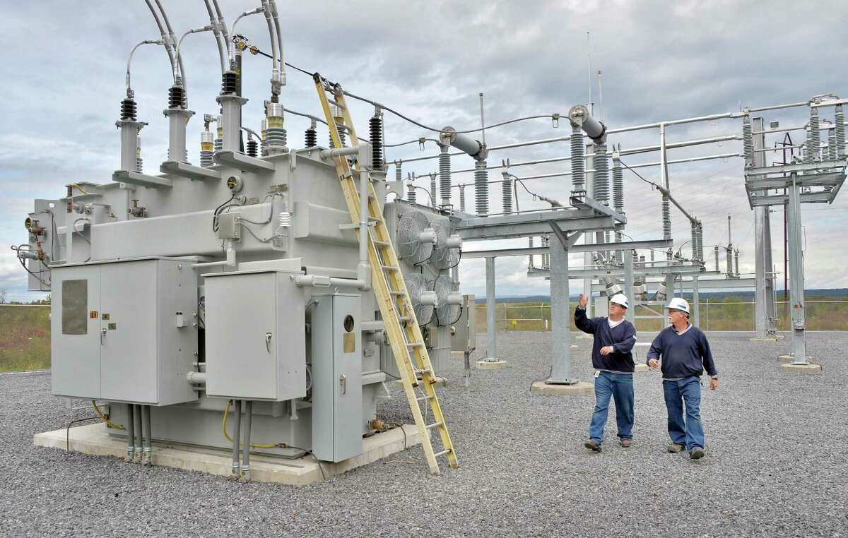 Chief electrician Tom Schener, right, and relay tester Bryan Simonik with the new 25 MVA transformer at National Grid's new substation rebuilt after Superstorm Sandy Tuesday, Oct. 7, 2014, in Amsterdam, N.Y. (John Carl D'Annibale / Times Union)