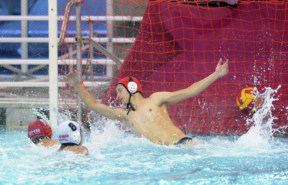 At left, Edward Moss (#11) of Greenwich scores on a diving Y Pro goalie Nikita Stepanov in a preliminary round match between Greenwich High School and Y Pro of Brooklyn, N.Y., during the 40th annual Cardinal Water Polo Tournament at the Greenwich High School pool, Saturday morning, Nov. 1, 2014. In the foreground is Alexander Vakhler (#8) of Y Pro. Greenwich won the match, 11-5. Photo: Bob Luckey / Greenwich Time